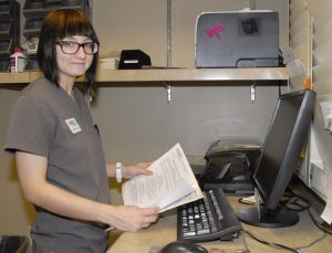 A team member smiling at the camera while she works in the back office on the computer